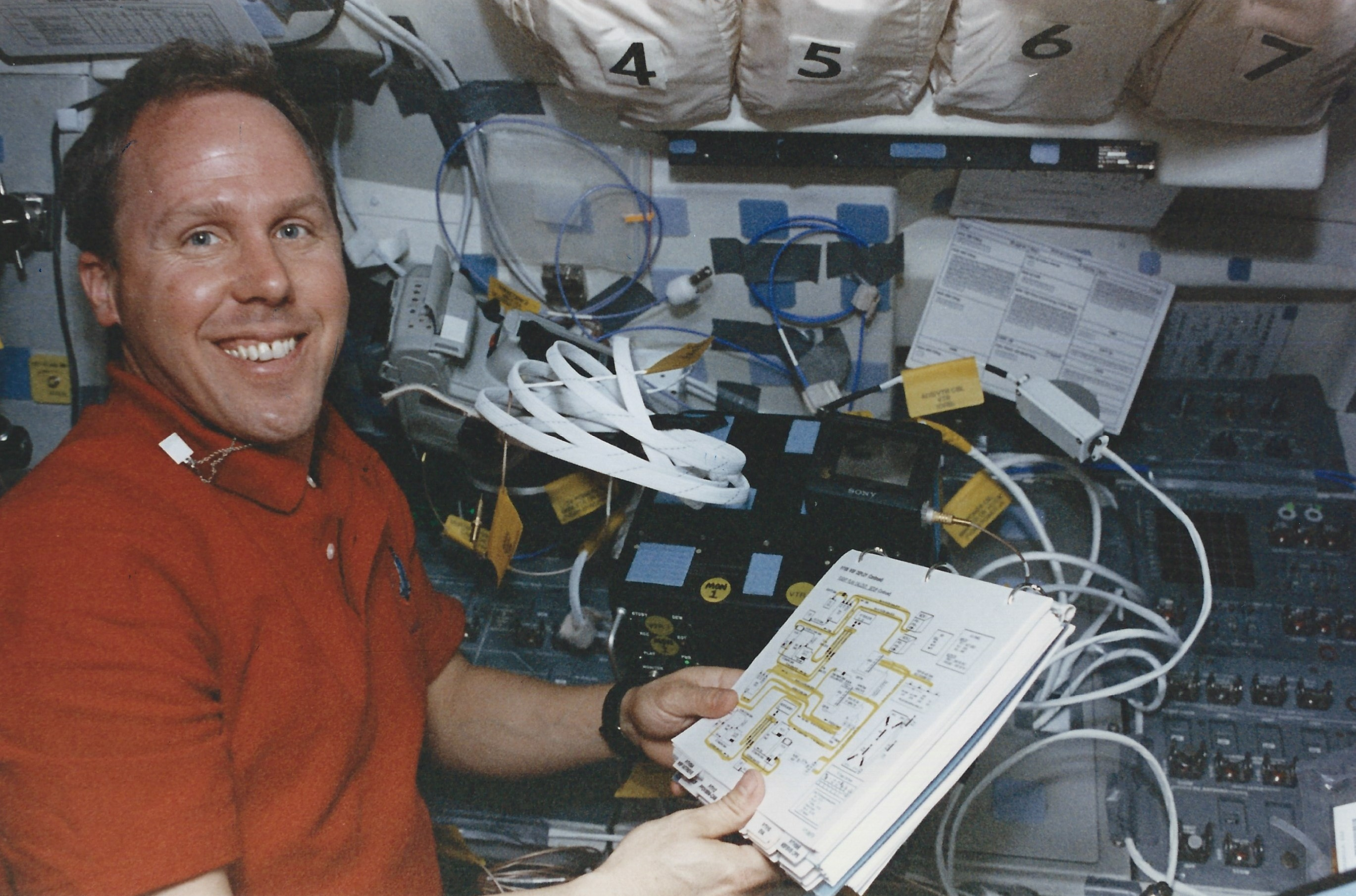 Tom Jones sets up photo-TV wiring on Columbia's aft flight deck. (NASA STS080-325-006)